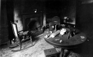 A bare, old fashioned room with an empty fireplace